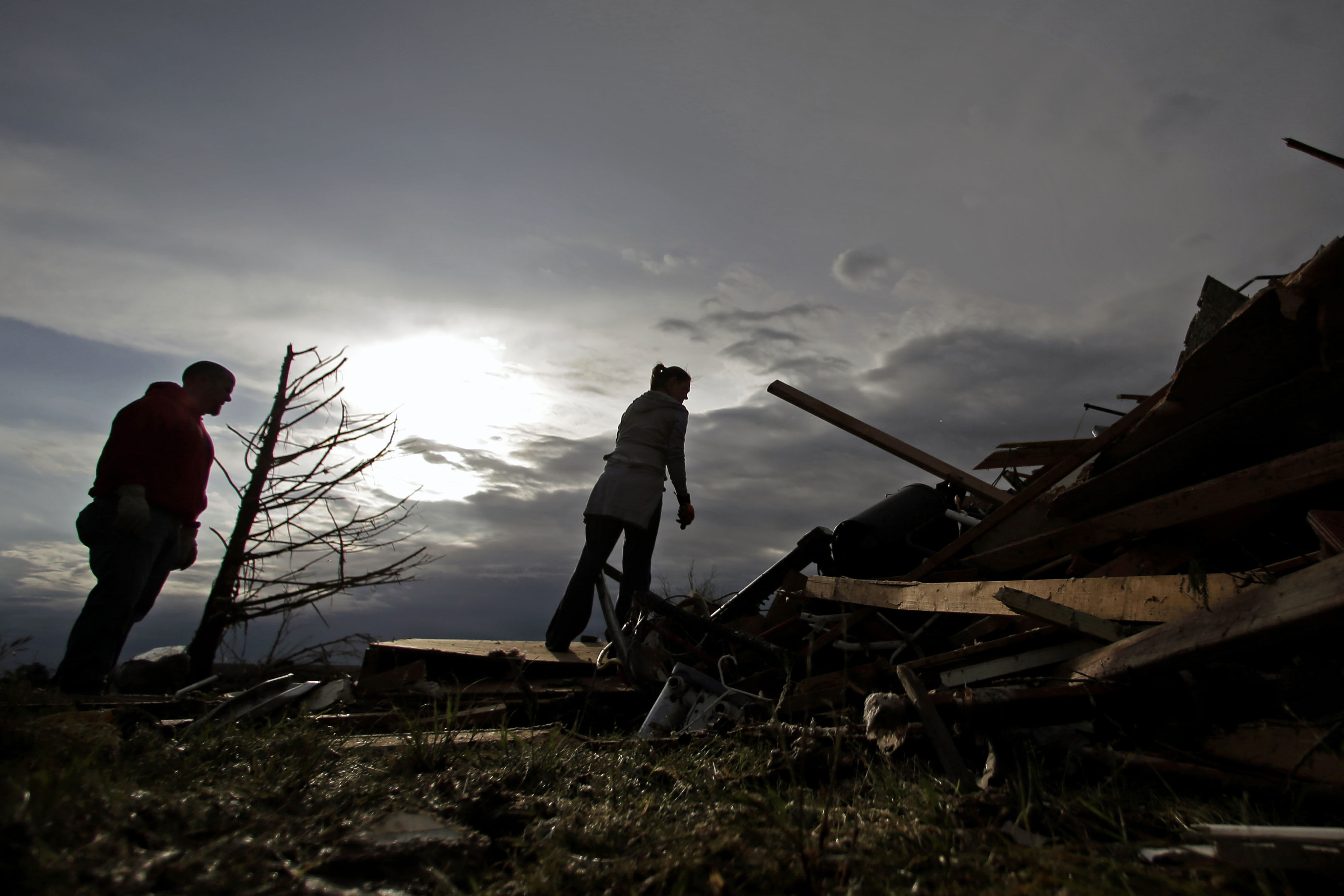 Zac and Denisha Woodcock look through the rubble of their tornado-ravaged home.