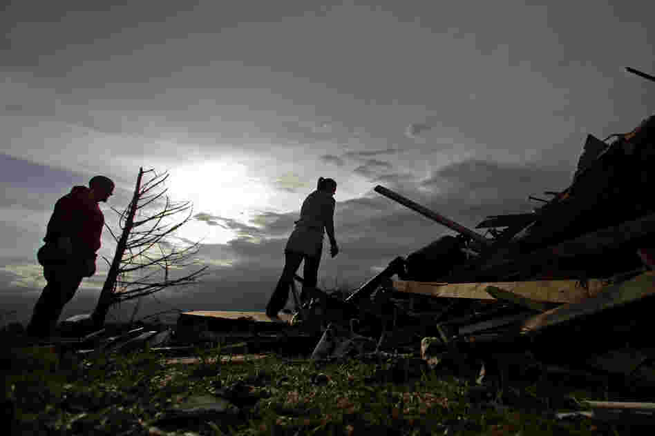 Zac and Denisha Woodcock look through the rubble of their tornado-ravaged home on Tuesday in Moore, Okla. A huge tornado roared through the Oklahoma City suburb Monday, flattening entire neighborhoods and an elementary school.