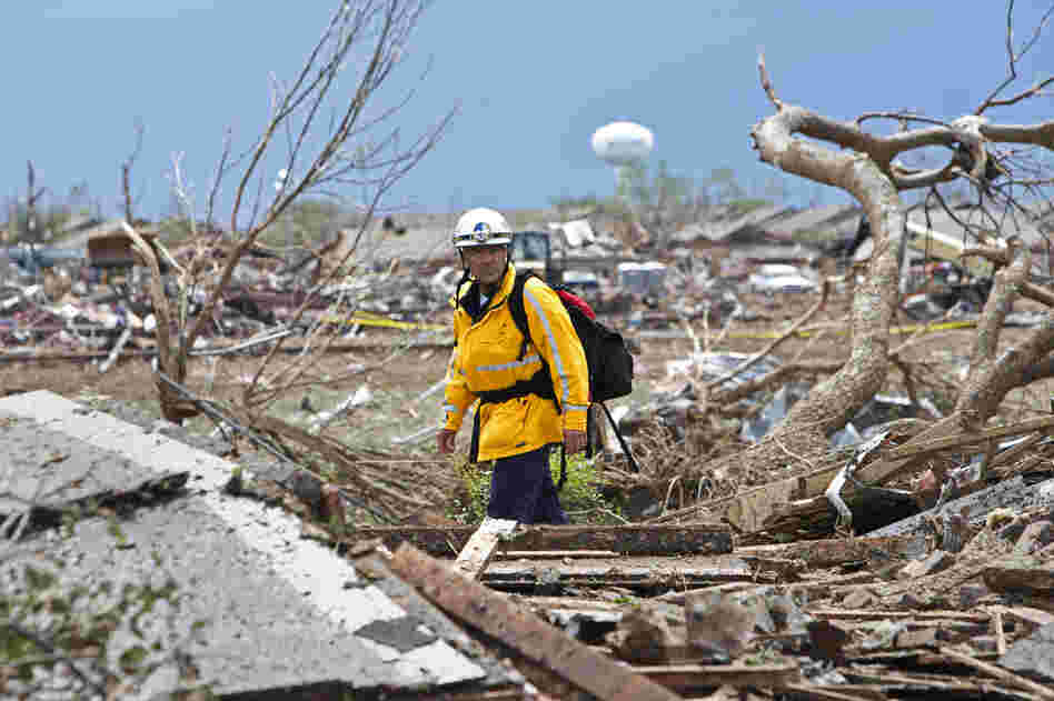 A rescue worker checks the rubble in a residential area in Moore, Okla., on Tuesday after a massive tornado struck the area on Monday. Emergency workers pulled more than 100 survivors from the rubble of homes, schools and a hospital in Moore.