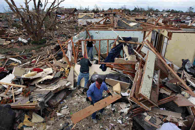 Jimmy Hodges works with Chad Heltcel and his wife, Cassidi, on Tuesday in the wreckage of Heltcel's family home in Moore, Okla.