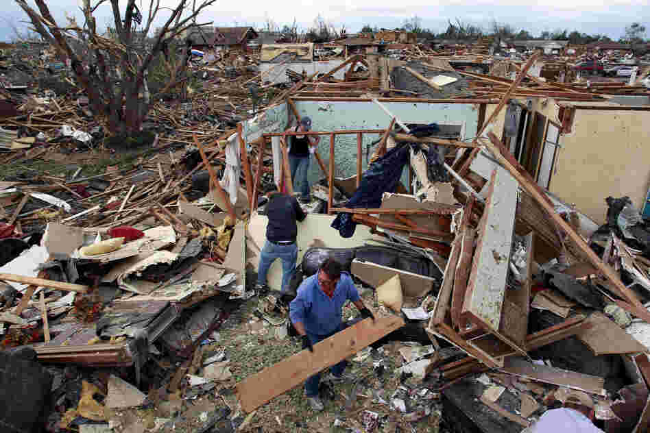 Jimmy Hodges helps Chad Heltcel and his wife Cassidi salvage the wreckage of Chad Heltcel's family home on Tuesday, which was destroyed Monday when a tornado moved through Moore, Okla. The National Weather Service now , this tornado produced winds in excess of 200 mph, making it a top-of-the-scale EF-5.