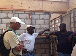 Tim Myers, founder of the Haiti School Project, talks with his construction foreman, Gilberte, and his translator, Matt.