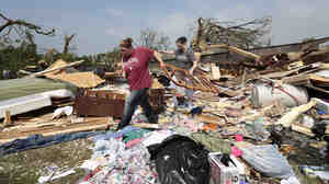 Aid groups are mobilizing relief efforts to help victims of the storm. Here, Candice Lopez, left, and Stephanie Davis help clean debris from Thelma Cox's mobile home near Shawnee, Okla., after it was destroyed Monday.