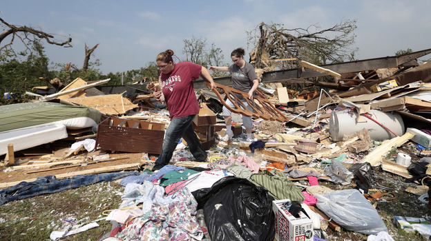 Aid groups are mobilizing relief efforts to help victims of the storm. Here, Candice Lopez, left, and Stephanie Davis help clean debris from Thelma Cox's mobile home near Shawnee, Okla., after it was destroyed Monday. (Getty Images)