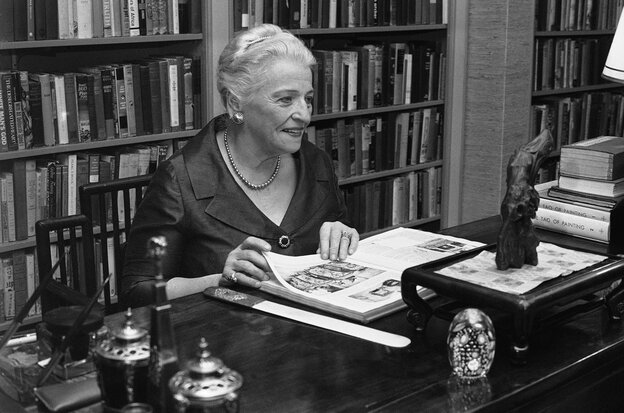 At her desk in the study of her Philadelphia townhouse in 1967, Pearl Buck looks at a bound volume of the magazine Asia from 1925 that  contained her first published work.