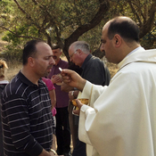Ibrahim Shomali, a Palestinian priest, offers Communion under the olive trees of the Cremisan Valley in the Israeli-occupied West Bank. This is part of a regular protest against Israeli plans to build a section of its West Bank barrier here, which would separate Palestinians from their agricultural lands.