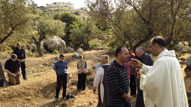 Ibrahim Shomali, a Palestinian priest, offers Communion under the olive trees of the Cremisan Valley in the Israeli-occupied West Bank. This is part of a regular protest against Israeli plans to build a section of its West Bank barrier here, which would separate Palestinians fr
