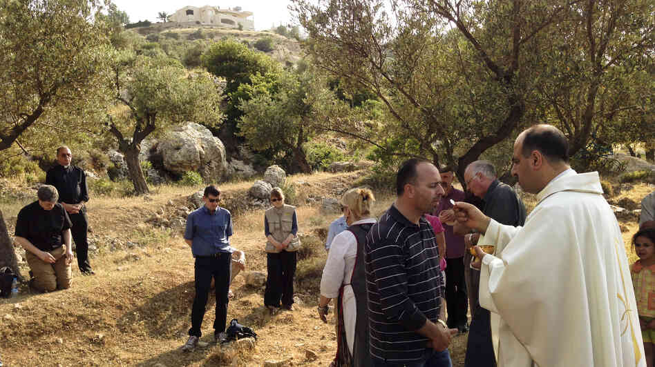 Ibrahim Shomali, a Palestinian priest, offers Communion under the olive trees of the Cremisan Valley in the Israeli-occupied West Bank. This is part of a regular protest against Israeli plans to build a section of its West Bank barrier here, which would