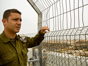 Israeli army Capt. Barak Raz stands on a concrete wall that is part of the barrier separating Israelis and Palestinians in the West Bank. Soldiers climb to this spot during Palestinian protests to disperse crowds with tear gas or a foul-smelling liquid nicknamed