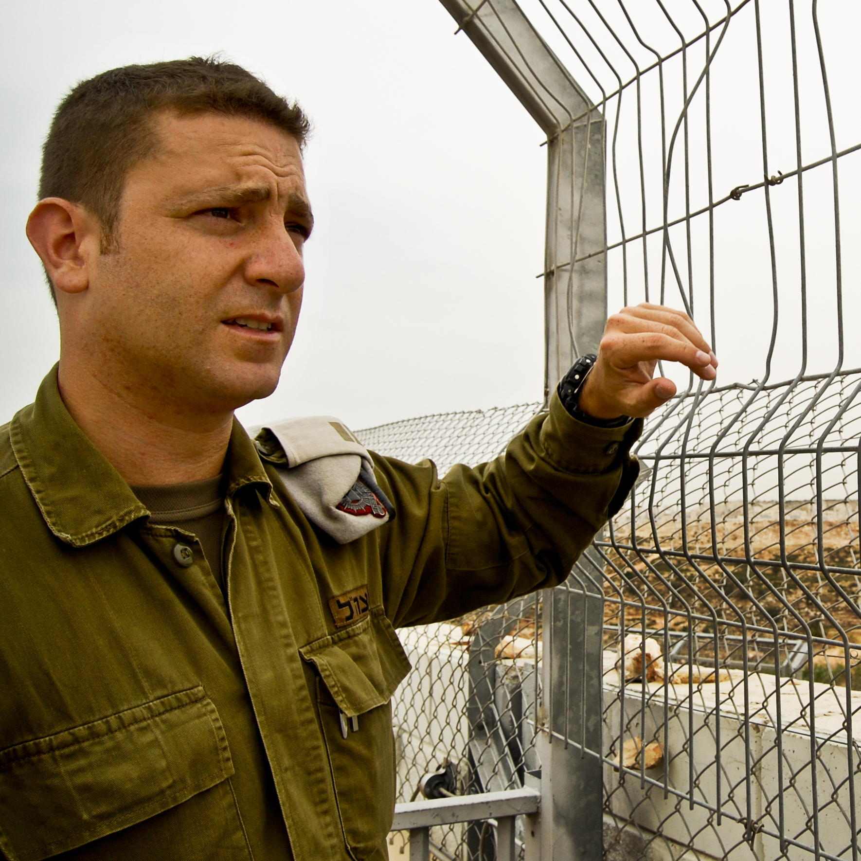 "Israeli army Capt. Barak Raz stands on a concrete wall that is part of the barrier separating Israelis and Palestinians in the West Bank. Soldiers climb to this spot during Palestinian protests to disperse crowds with tear gas or a foul-smelling liquid nicknamed ""skunk."""