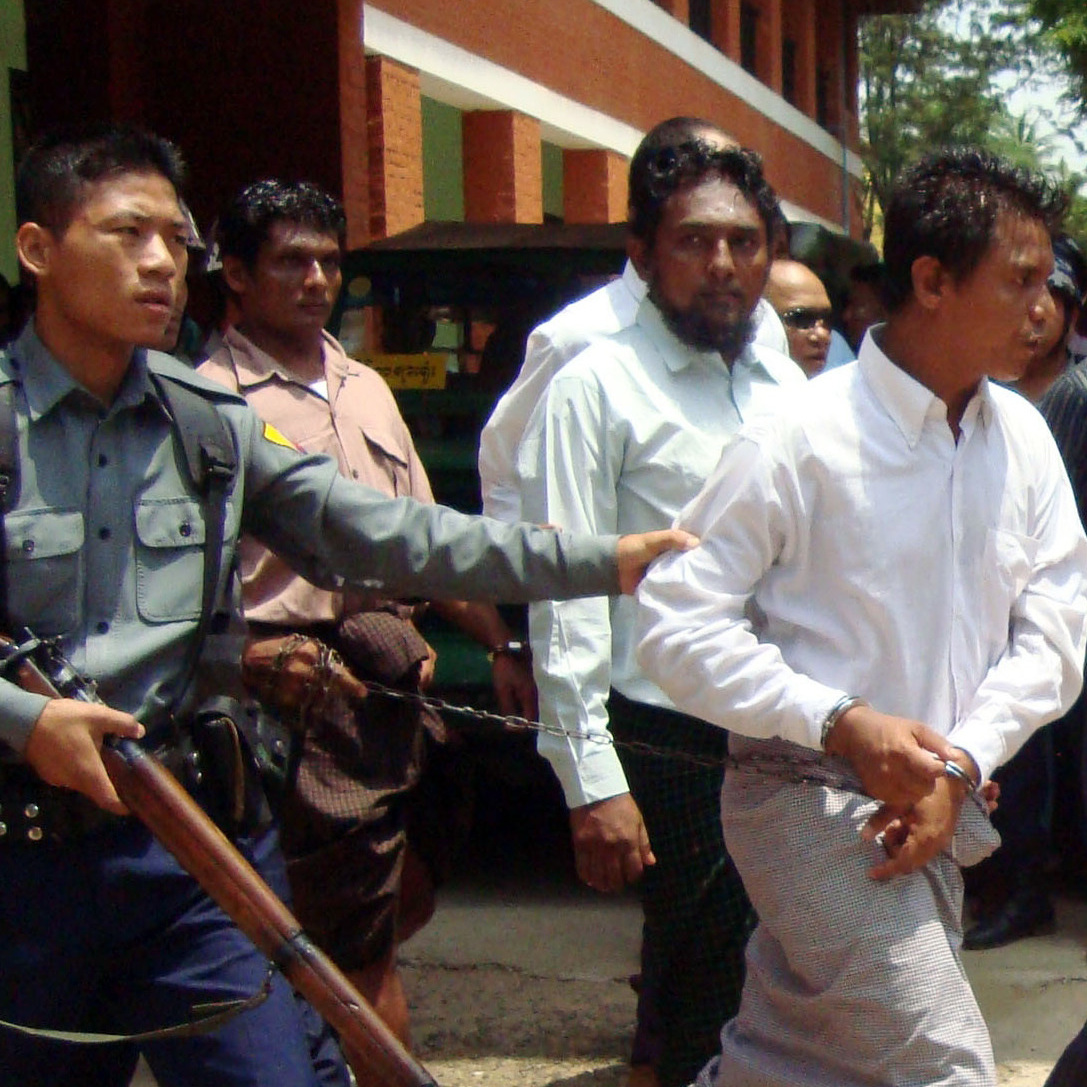 A Muslim man is escorted by police officers following a trial at a township court in Meikhtila, central Myanmar, on Tuesday. A court in Myanmar sentenced seven Muslims to terms ranging from two years to life in prison Tuesday for the killing of a Buddhist monk during sectarian violence, which poses a serious challenge to President Thein Sein's reformist government.