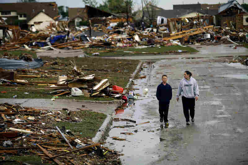 A woman and young boy walk along a street amid destroyed houses Tuesday in Moore, Okla. The National Weather Service now says Monday's tornado produced winds in excess of 200 mph, making it a top-of-the-scale EF5.