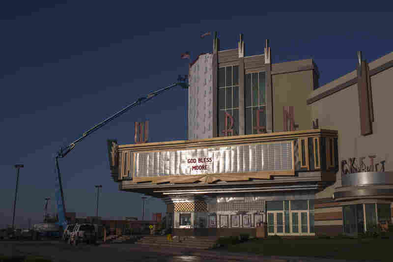 "A sign reads ""God Bless Moore"" as workers make repairs to Warren Theatre after the Oklahoma City suburb of Moore was devastated by a tornado."