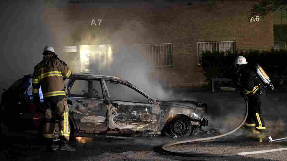 Swedish firemen extinguish a burning car Tuesday after youths rioted for a third night in a row in the suburbs of Stockholm. The unrest began after police said they shot dead a 69-year-old man wielding a machete in an immigrant neighborhood.