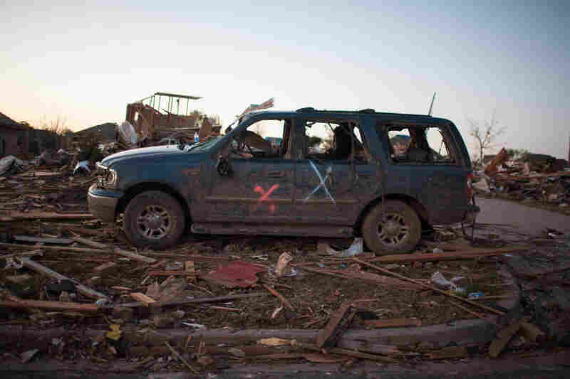 A battered vehicle sits amid the ruins following the Monday's tornado.