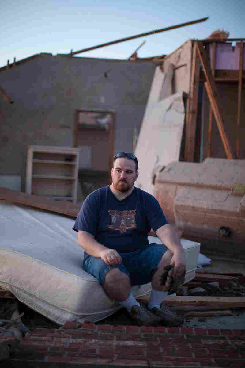 Matt Claxton sits before his shattered house. He and his wife and their two dogs rode out the storm in a neighbor's shelter across the street from their home in Heatherwood. The area behind Claxton is the room they had planned to shelter in.