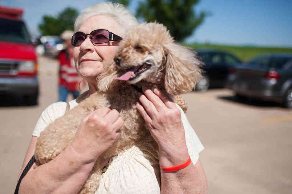 Marylin Degman holds her 10-year-old toy poodle, Angel Baby, on Wednesday outside the First Baptist Church in Moore, Okla.