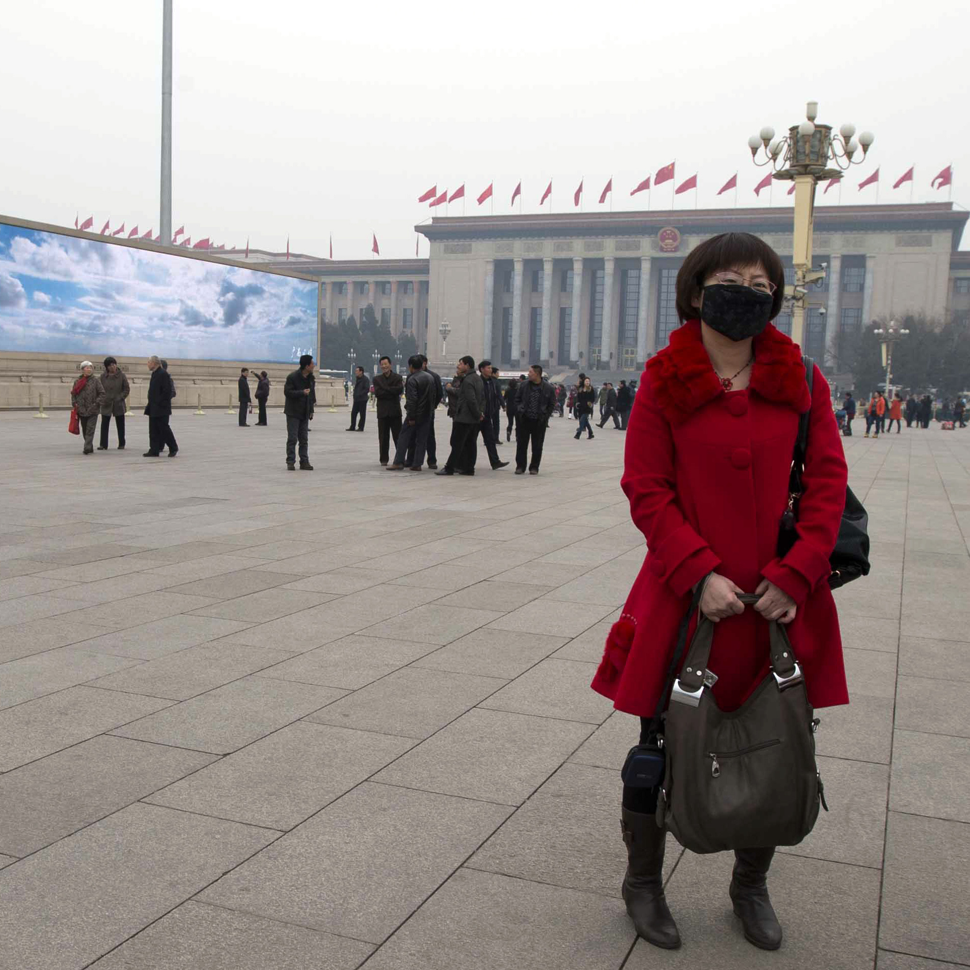 A woman wears a mask as she stands near a giant display depicting blue skies during a day of heavy pollution on Tiananmen Square in Beijing on March 6.
