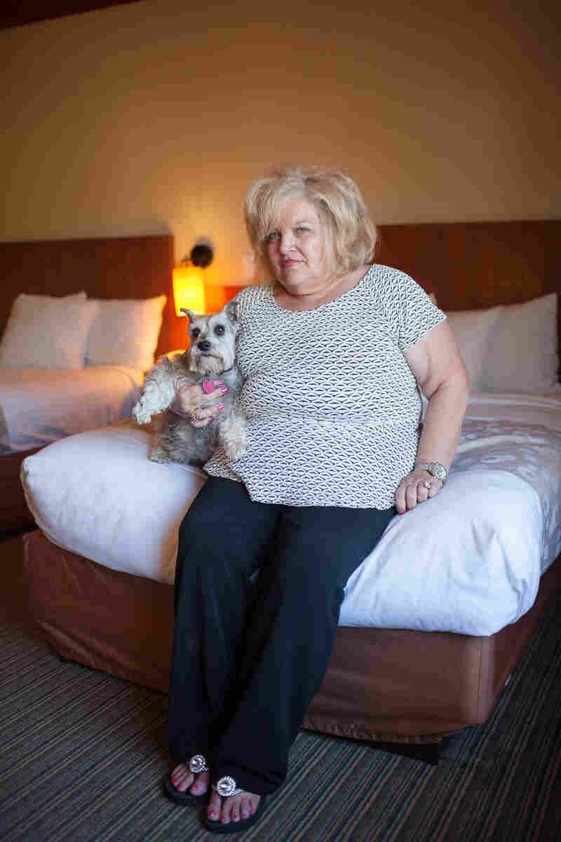 Kathy Hughes sits with her dog Gracie at the La Quinta in Norman, Okla., on Wednesday. This is their third night at the La Quinta, which is one of the few area hotels accepting people and their pets.
