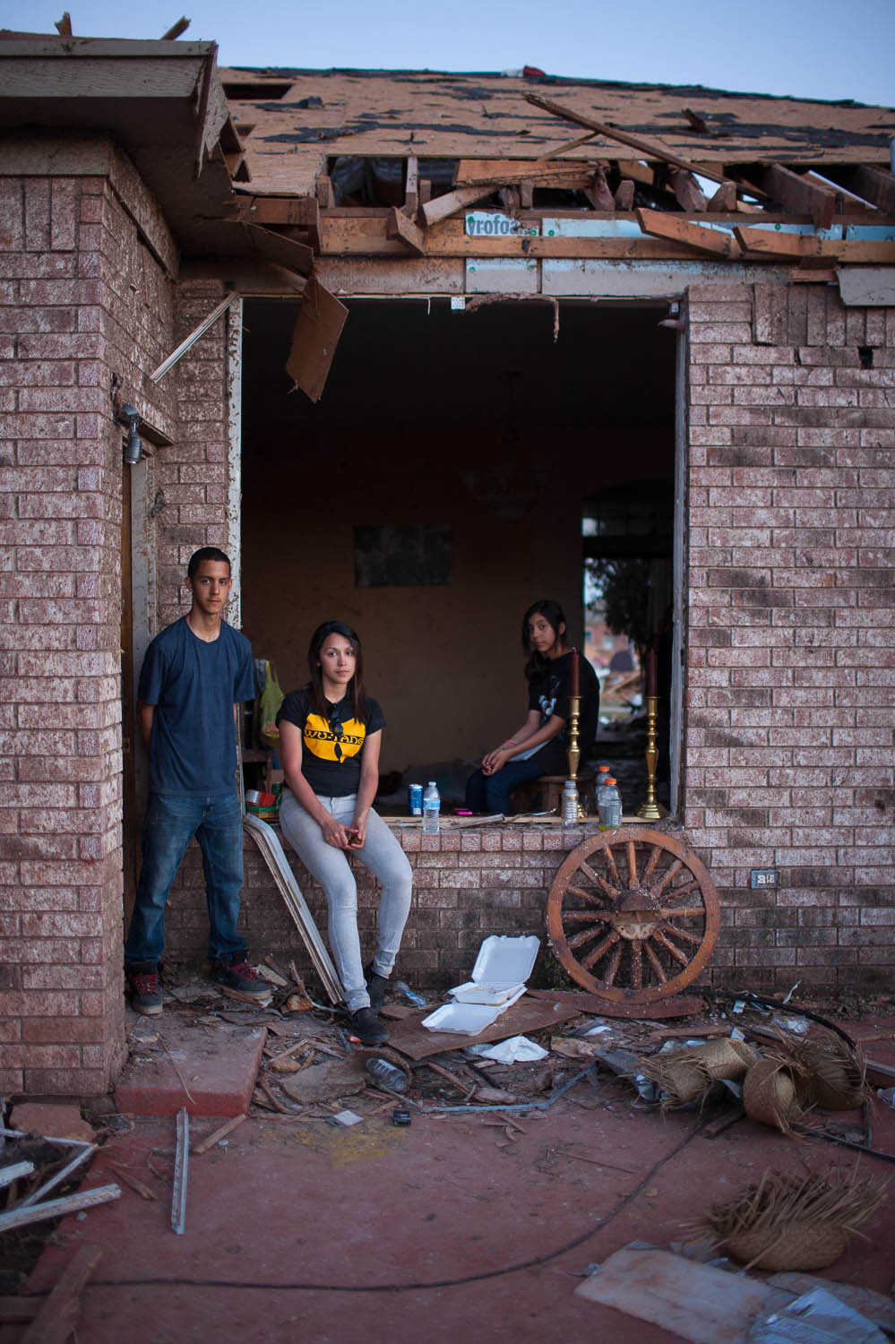 Siblings (from left) Alan, Sylvia and Ariel Trillo pose at their home in the Heather Wood subdivision in Moore. The Trillo home is one of the few homes there that is still standing, though everything inside is damaged.