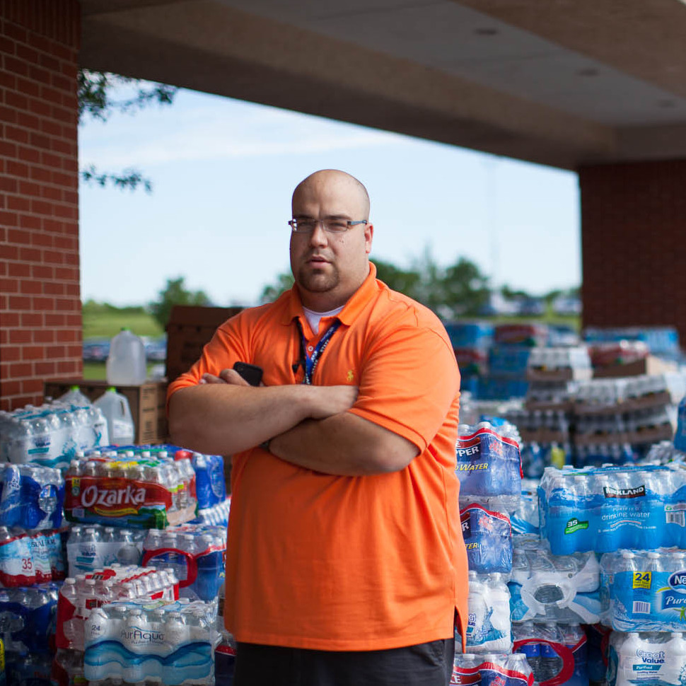 Kyle Duncan, the business administrator at the First Baptist Church, stands by the donation staging area where people have dropped off goods.