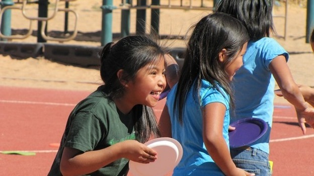 An elementary school student enjoys Field Day on a playground. Harold Begay, superintendent of the Tuba City Unified School District in Arizona, says the repairs that are needed to playground equipment, school buildings and buses would no€™t be allowed anywhere else. (KJZZ)