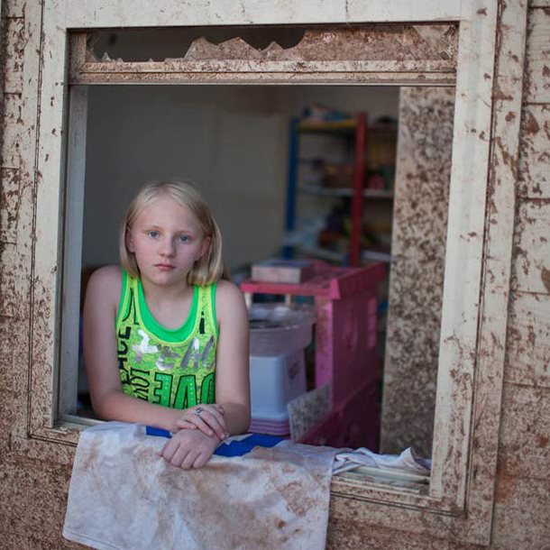 Sara Hock, 11, poses for a portrait in her bedroom window. Sarah was at school during the tornado, while her father, Brian Hock, took shelter.