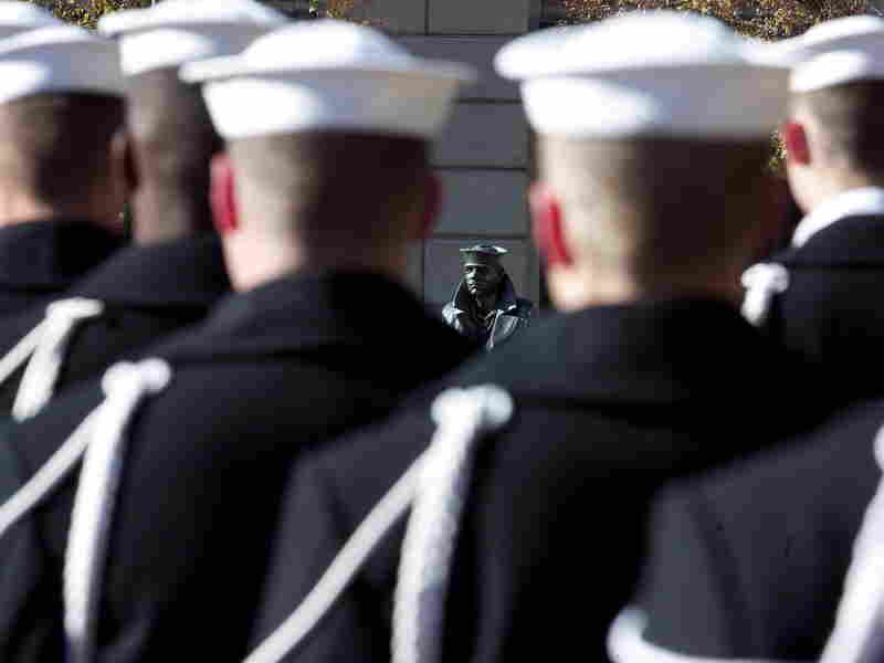 U.S. Navy sailors form a ceremonial guard at a wreath-laying ceremony to memorialize the victims of the attack on Pearl Harbor and pay tribute to the veterans of World War II in front of the Lone Sailor statue at the Naval Memorial in Washington, D.C., in December 2003.