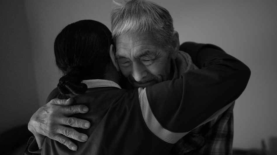 Frankie Kuzuguk, 82, gets a hug from his daughter Marilyn Kuzuguk at Quyanna Care Center in Nome, Alaska, after receiving an official honorable discharge and a distinguished service coin from visiting Veterans Affairs officials. The VA is still tracking down the few surviving members of the World War II Alaska Territorial Guard or delivering benefits to their next of kin. (David Gilkey/NPR )