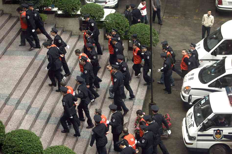 Chinese police lead a group of defendants, including millionaire and politician Li Qiang, to court on organized crime charges in 2009. Many of those arrested in now-imprisoned politician Bo Xilai's campaign against the mafia still remain in jail, despite serious legal questions about the process.