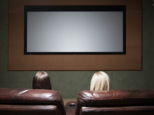 Two women watch a movie screen.