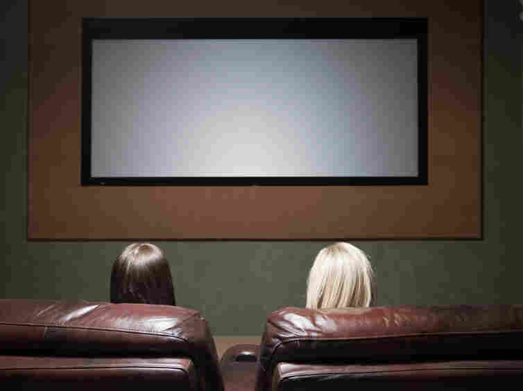 Two women watch a movie screen.