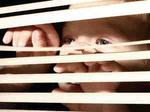Boy looking through window blinds