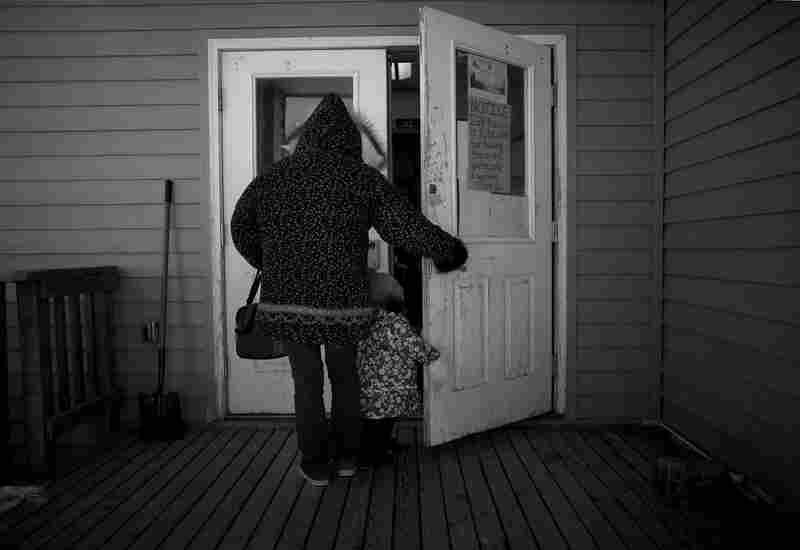 A woman holds the door for her daughter at the entrance to the Wales community center, where a meeting for local veterans turned into a gathering for many of the villagers in the tiny town.