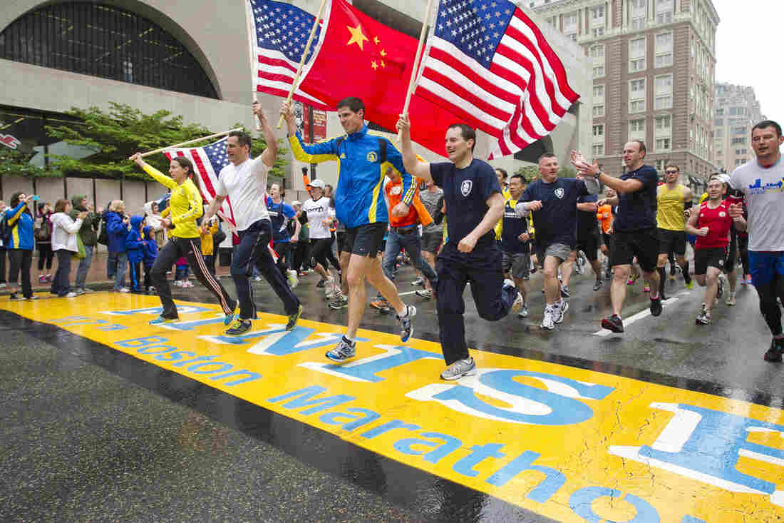 """Runners holding American flags and a Chinese flag cross the finish line after completing the final mile of the Boston Marathon course during """"#onerun"""" in Boston, Massachusetts on Saturday."""