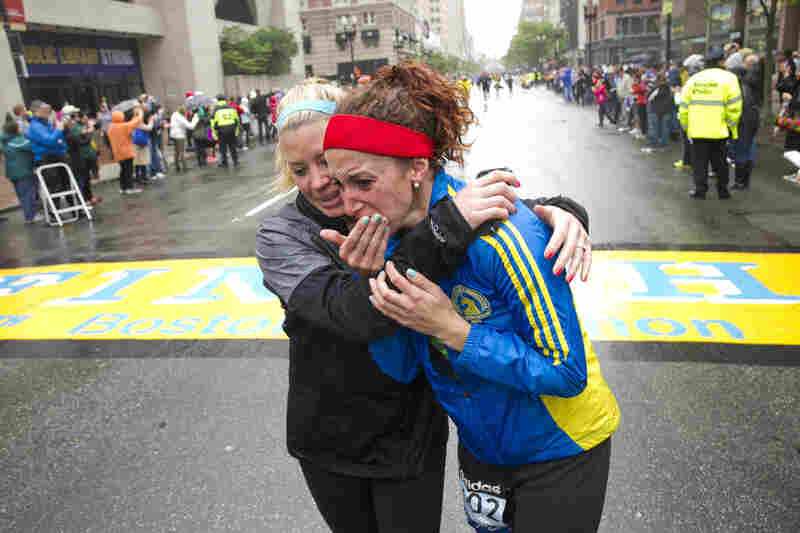 """Erin Roy, left, comforts Elise Wulff as runners cross the finish line after completing the final mile of the Boston Marathon course during """"#onerun"""" in Boston, Massachusetts, on Saturday."""