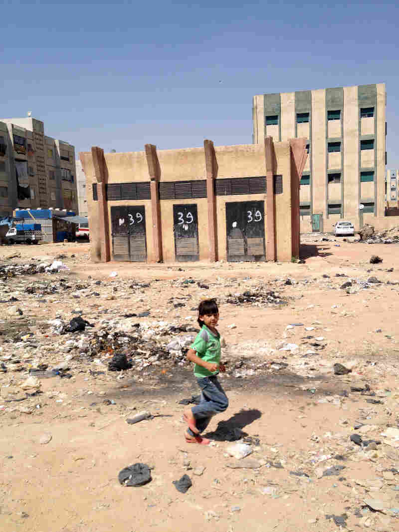 A child plays in a dusty courtyard of half-finished apartment buildings, now housing refugees, in a suburb of Damascus. The complex is deemed safe because artillery has landed across the street but not yet here.
