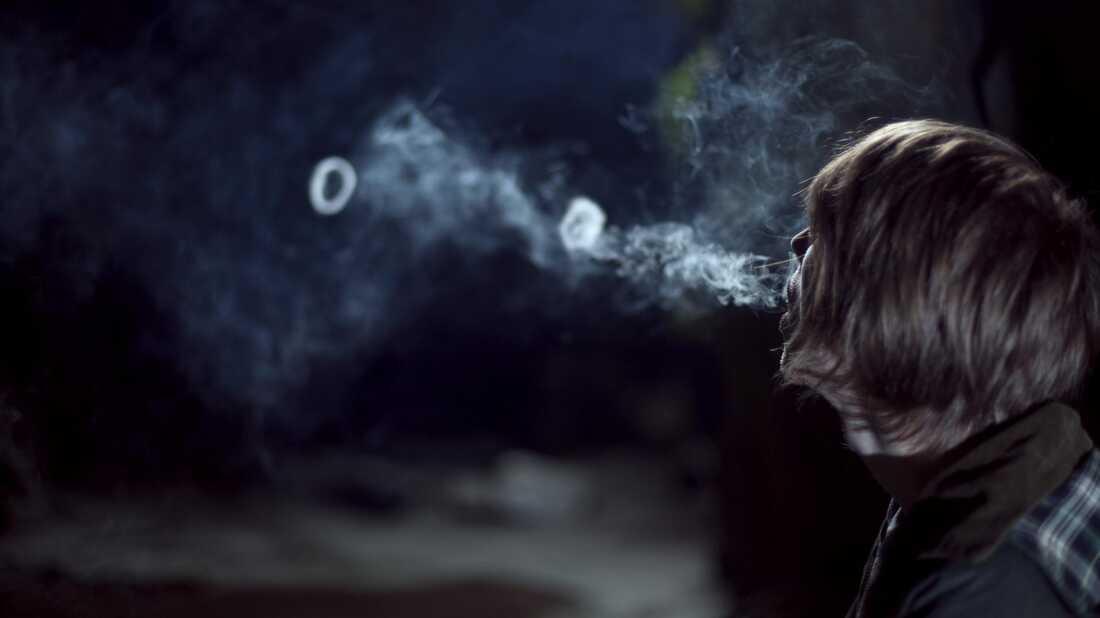 A human blowing smoke rings.