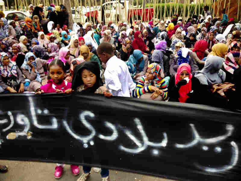 """Residents of the Libyan town of Tawargha were driven from their homes in Libya's 2011 civil war. Girls from the town hold up a sign that says """"we want our homeland, Tawargha"""" during a protest outside Libya's Parliament. Residents say they will return next month, which could lead to a showdown."""