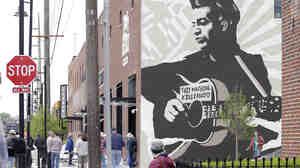 "Outside the Woody Guthrie Center, there's a large mural of Guthrie holding his guitar bearing the phrase, ""This Machine Kills Fascists."""