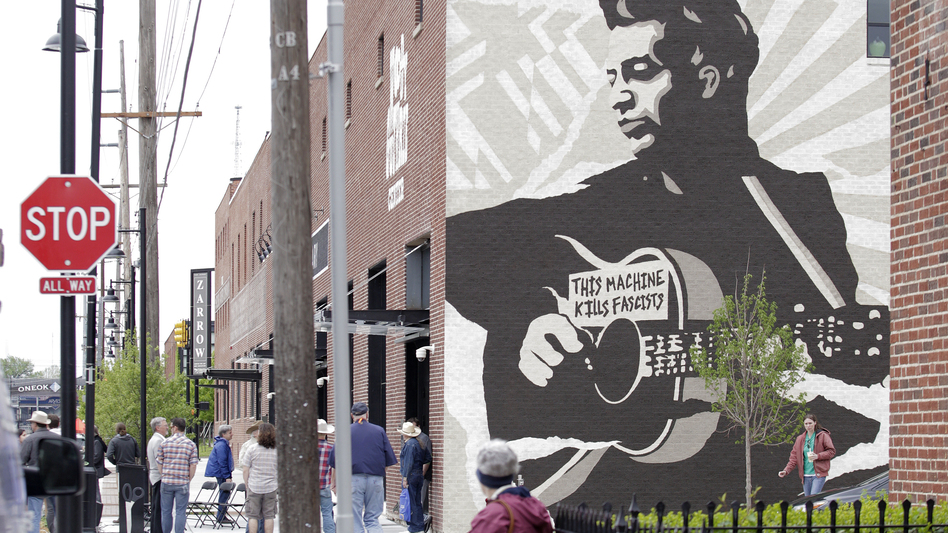 "Outside the Woody Guthrie Center, there's a large mural of Guthrie holding his guitar bearing the phrase, ""This Machine Kills Fascists."" (WireImage)"