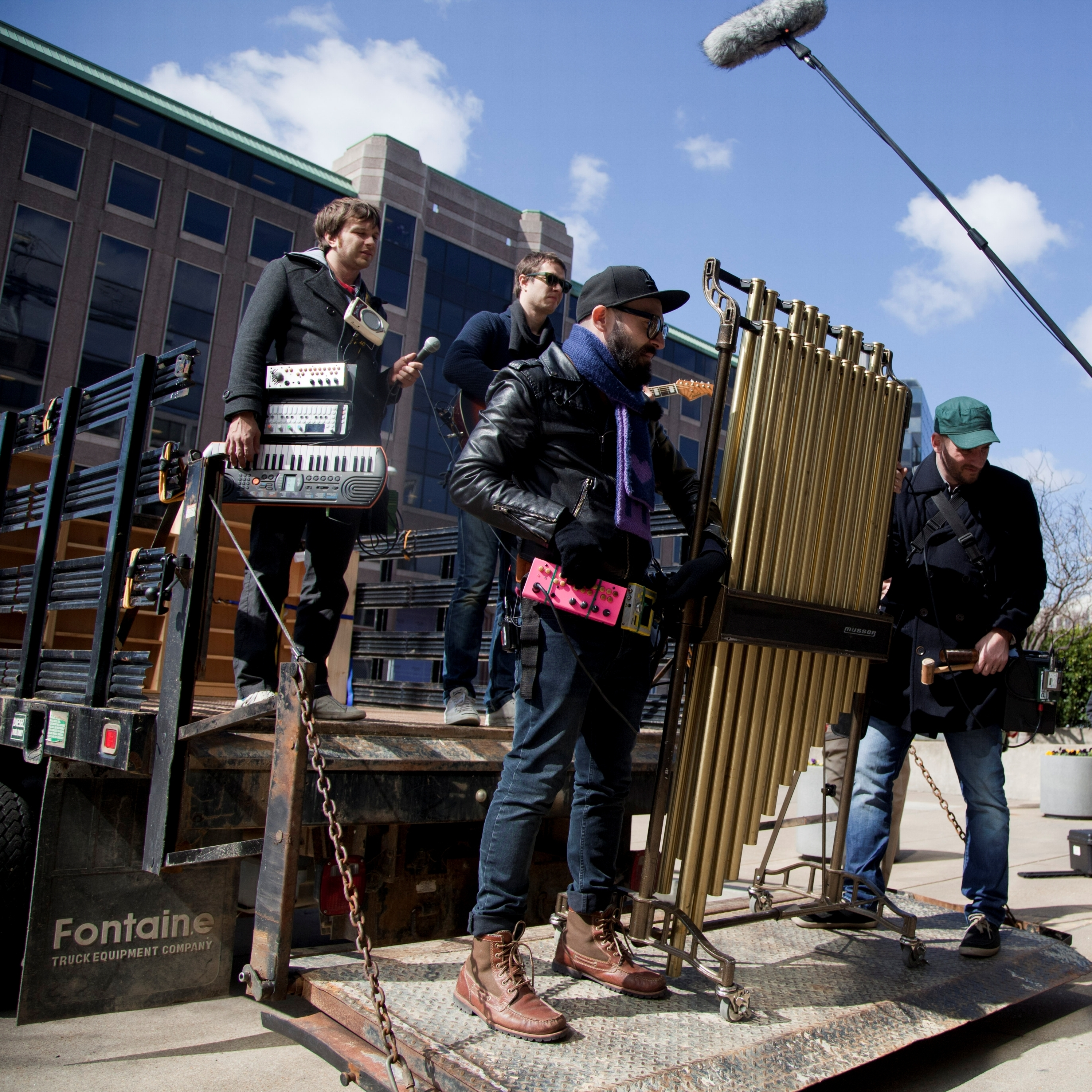 NPR Music's Mito Habe-Evans (bottom right) holds the digital clapperboard before a take outside NPR's old headquarters.