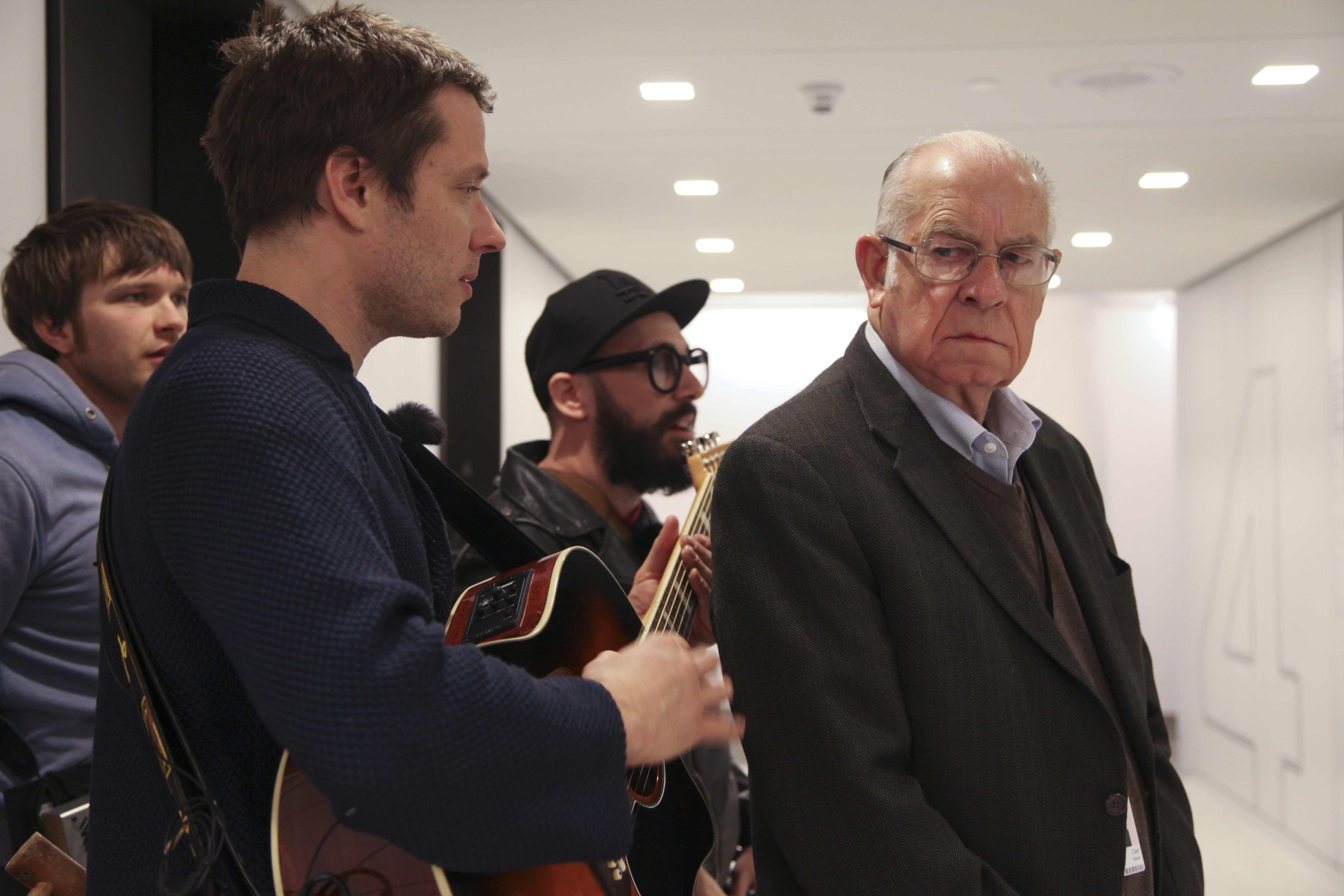 Carl Kasell, Wait Wait...Don't Tell Me! Judge and Scorekeeper, casts a sideways glance at the band during his scene, which takes place in an elevator of NPR's new headquarters.