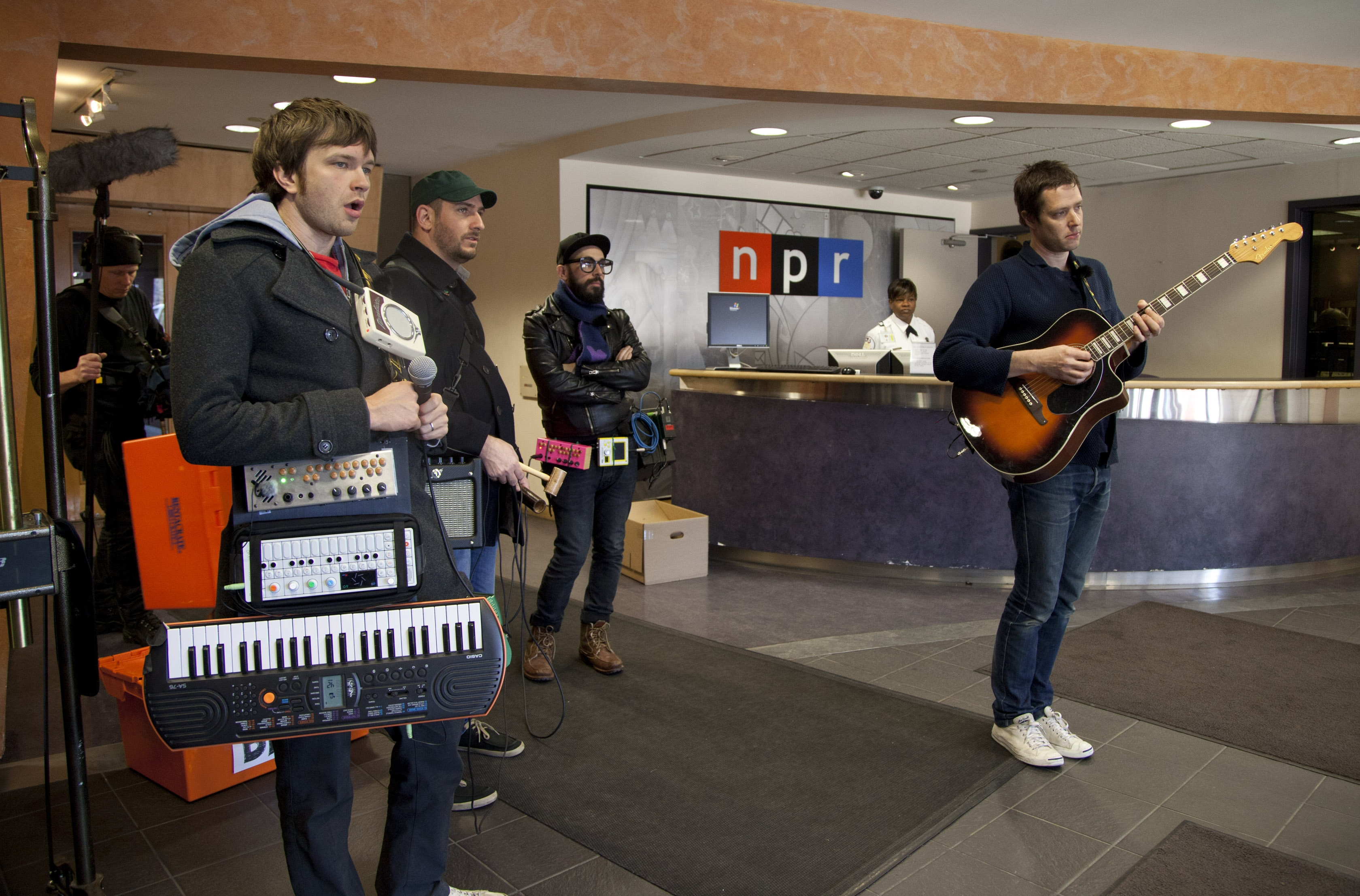Bandmates from the power-pop band OK Go hang out between takes during a scene for NPR Music's Tiny Desk Concert inside NPR's old headquarters lobby. Andy Ross (left), Dan Konopka, Tim Nordwind and Damian Kulash