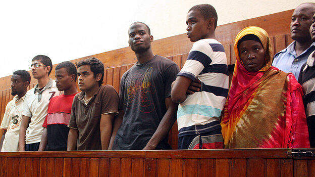 A Nov. 23, 2010, photo shows Michael Adebolajo (center, in dark T-shirt) with suspected Al-Shabab recruits who were arrested by Kenyan police. Adebolajo, one of the main suspects in the brutal murder of a soldier in London