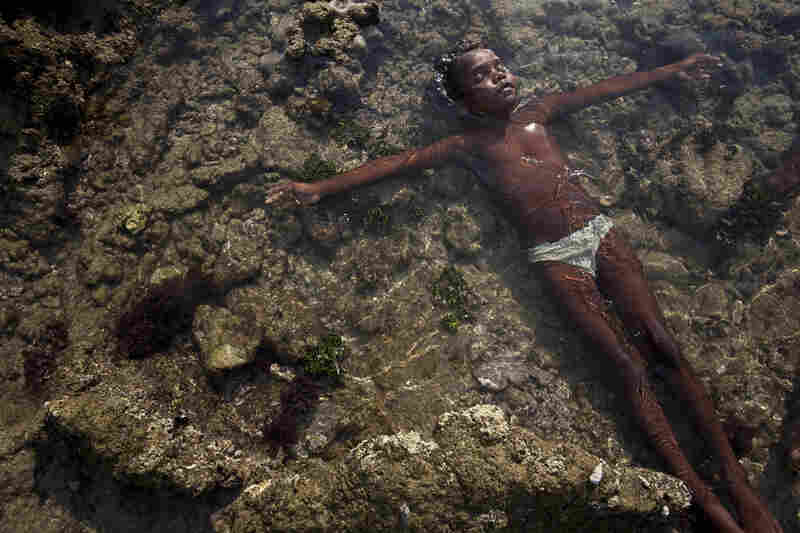 Mawunmula Garawirrtja cools off in a tidal pool while gathering food at low tide with her grandmother.