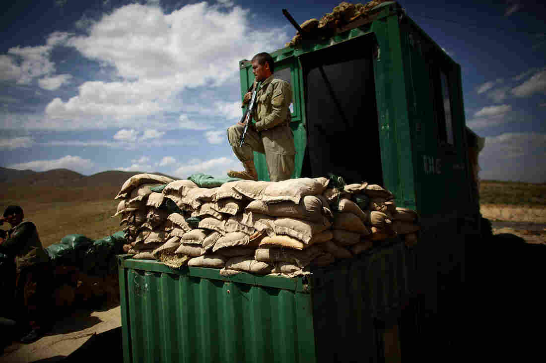 An Afghan policeman stands on a shipping container that's been turned into a makeshift checkpoint on a road leading into Sayed Abad. The Taliban have been active in the area, and securing the roads remains a major challenge.