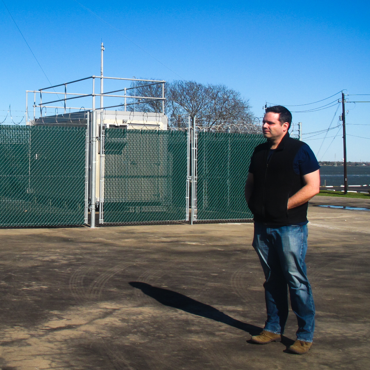 Matthew Tejada stands near an air monitoring station.