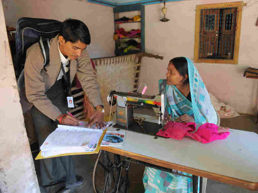 An official from a microfinance company talks with a borrower in Vadod, India.