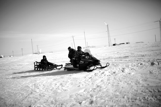 Local veterans representative Sean Komonaseak drives a snowmobile with the VA's Tommy Sowers (back seat) and Sean Foertsch across the ice to the village of Wales, Alaska.
